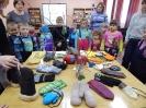 Малыши рассматривают выставку с рукавичками, варежками, перчатками для разных возрастов и профессий