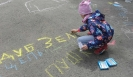 Участница акции «Классика на каждом шагу» пишет мелом на асфальте строчки из пушкинских стихотворений